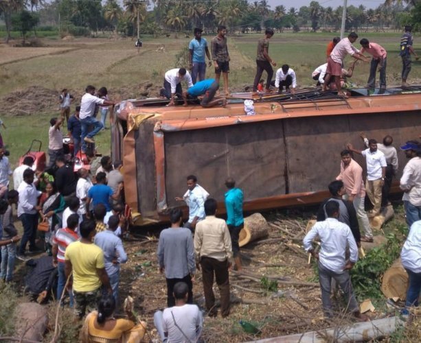Locals rescue the passengers from the bus that turned turtle in Maddur, Mandya district, on Sunday. DH PHOTO
