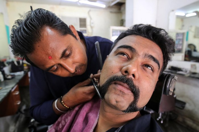 Dhiren Makvana gets his moustache trimmed similar to the one sported by Indian Air Force pilot Abhinandan Varthaman, who was captured and later released by Pakistan, inside a salon in Ahmedabad, India, March 4, 2019. (REUTERS)