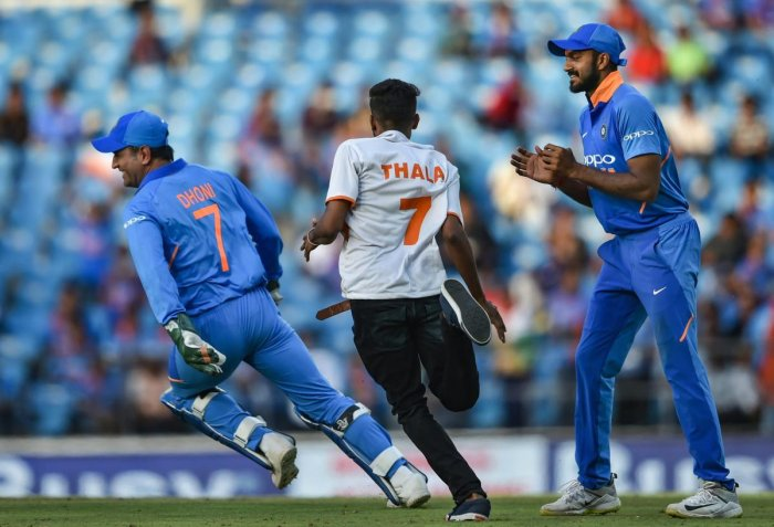 CATCH ME IF YOU CAN: India's MS Dhoni runs away from a pitch-invader during the second ODI against Australia at the Vidarbha Cricket Association Stadium in Nagpur. PTI