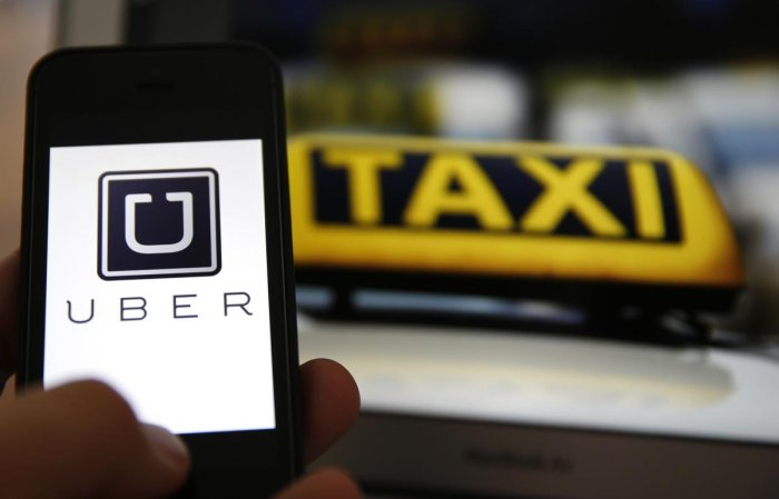 An illustration picture shows the logo of car-sharing service app Uber on a smartphone next to the picture of an official German taxi sign in Frankfurt, September 15, 2014. A Frankfurt high court will hold a hearing on a recent lawsuit brought against Ube
