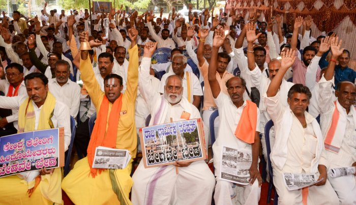 Priests stage a protest seeking government meet their various demands at Freedom Park in Bengaluru on Thursday. DH Photo