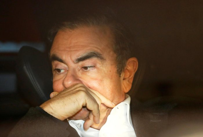 Former Nissan Motor Chairman Carlos Ghosn sits inside a car as he leaves his lawyer's office after being released on bail from Tokyo Detention House, in Tokyo. Reuters file photo