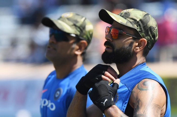 Indian cricket captain Virat Kohli and Mahendra Singh Dhoni (R) wear camouflage army caps ahead of the third one-day international (ODI) cricket match between India and Australia at the Jharkhand State Cricket Association International Cricket Stadium in