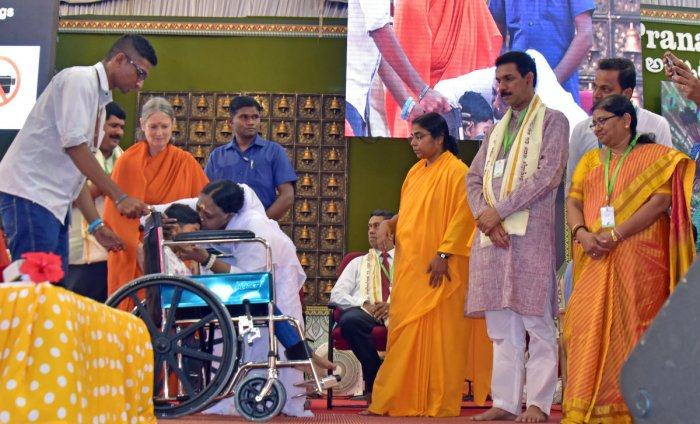 Mata Amritanandamayi blesses a specially abled child while distributing wheelchair during 'Amritasangama - 2019', on the premises of Amrita Vidyalaya at Boloor in Mangaluru on Friday. Dakshina Kannada MP Nalin Kumar Kateel, MLA D Vedavyas Kamath, Corporation Bank MD and CEO P V Bharati and others look on.