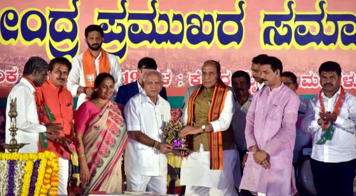 State BJP President B S Yeddyurappa hands over a memento to Union Home Minister Rajnath Singh during the convention of Shakthi Kendra Pramukhs from three Lok Sabha constituencies (DK, Udupi-Chikmagaluru and Shimoga) at Nehru Maidan in Mangaluru on Saturda