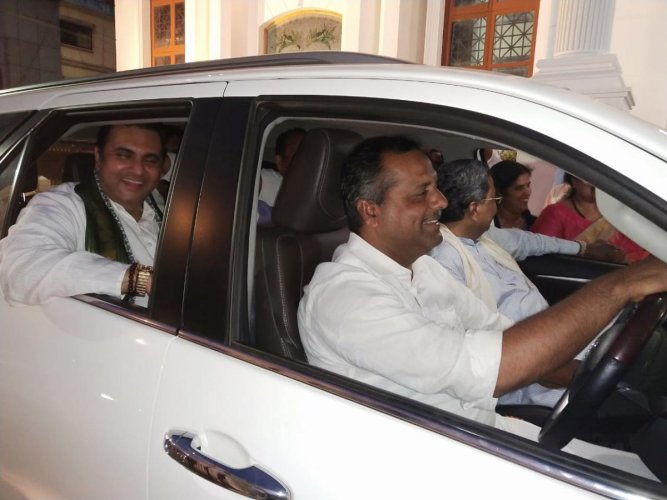 Minister for Urban Development U T Khader drives the former chief minister Siddaramaiah to the Congress rally venue after they were forced to abandon their official cars following the enforcement of Model Code of Conduct, in Udupi on Sunday evening. DH PH