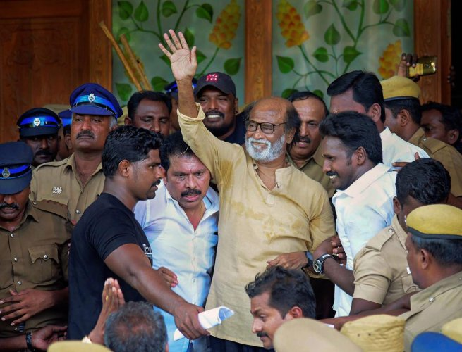 Actor-turned-politician Rajinikanth waves at supporters as he comes out of a government hospital after visiting those who got injured Tuticorin police firing, in Madurai on Wednesday. PTI