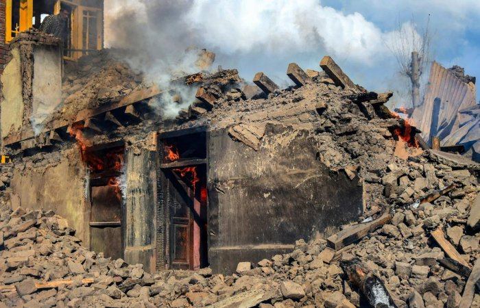 Smoke rises from a house destroyed during a gunbattle between security forces and militants at Reshi Mohlala area of Tral in Pulwama district of South Kashmir, Tuesday, March 5, 2019. Two local militants of the Hizbul Mujahideen have been killed in an ove