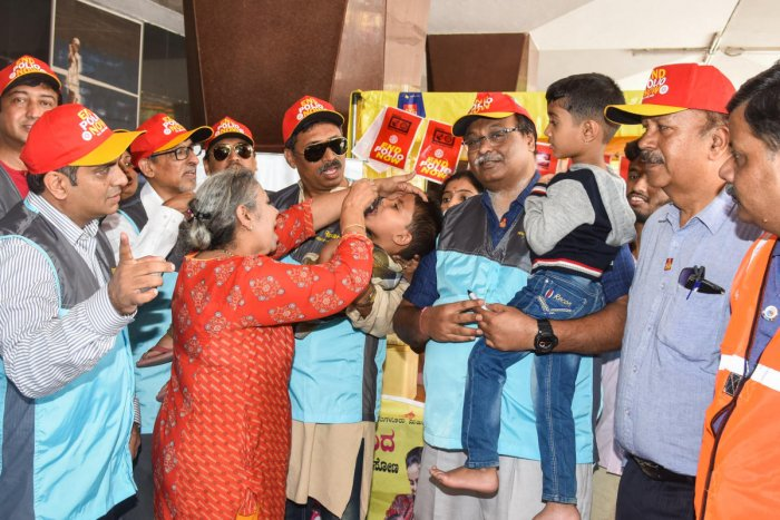 Suresh Hari, Governor Rotary District 3190 and Anitha Hari, First Lady Rotary 3190,administer polio drops to a child, as part of National Pulse Polio drive, at KSR City RailwayStation on Sunday. Dr Sameer Gowtham, president, Rotary Lalbagh; Shashikanth V