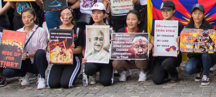 Tibetan women hold posters during a protest rally on account of 60th Tibetan National Uprising Day in MG Road junction, Bengaluru on Sunday.DH Photo/Prarthan D R