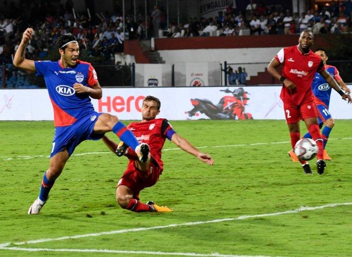 DEFT: Bengaluru FC's Miku (left) scores his team's first goal against NorthEast United FC at the Sree Kanteerava Stadium in Bengaluru on Monday. DH PHOTO/BH SHIVAKUMAR