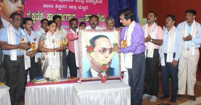 DDPI Sheshashayana Karinja inaugurates the district-level education convention in Udupi by garlanding the portrait of Ambedkar.