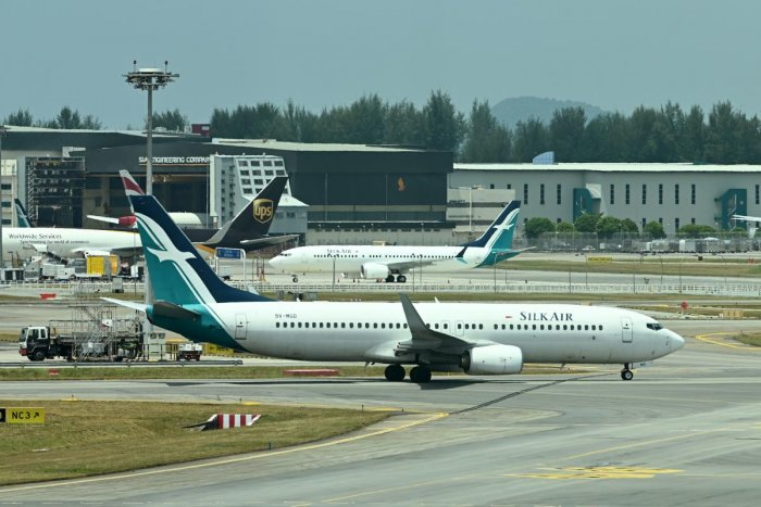 A SilkAir Boeing 737 MAX aircraft (background C) is parked on the tarmac of Changi International Airport in Singapore. AFP photo
