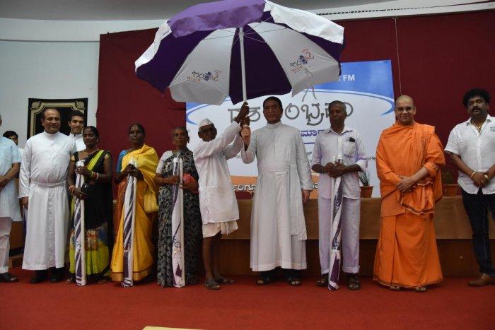St Aloysius College Principal Dr Praveen Martis presents an umbrella to M M Bilagi, popularly called 'Samosajja', at the decennial celebrations of Radio Sarang.