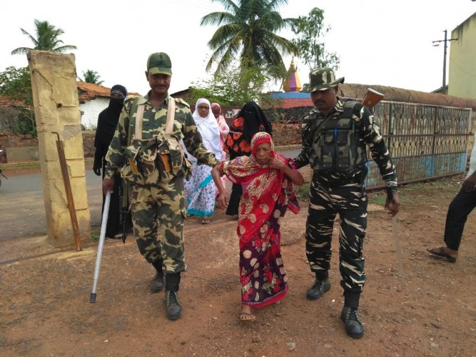 CRPF personnel helping a 90-year-old to reach out to the polling booth at Yamakanamaradi ST reserved constituency in Belagavi district.