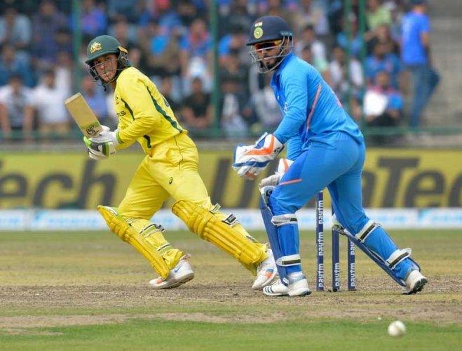 Usman Khawaja plays a shot as Rishabh Pant looks on during the fifth one-day international (ODI) cricket match between India and Australia at the Feroz Shah Kotla Stadium in New Delhi. (AFP Photo)