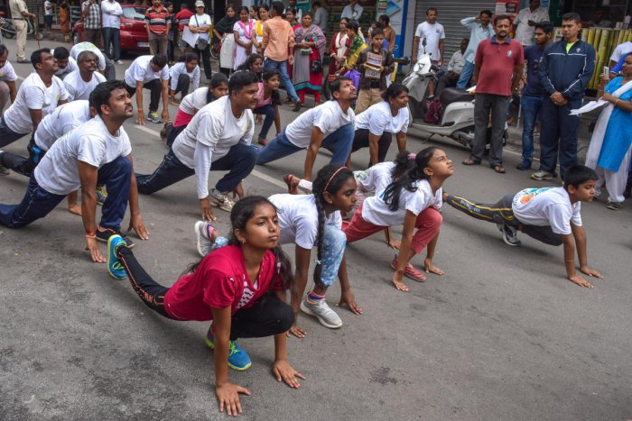 Yoga students hold a yoga demonstration to create awareness ahead of the International Yoga Day, in front of Ganesha Temple in Lakasandra on Sunday. Photo/S K Dinesh