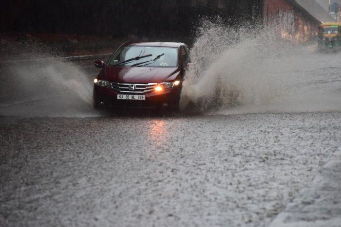 A car on a water-filled Vani Vilas Road near National College in Basavanagudi on Saturday. DH PHOTO/Chandrahas Kotekar