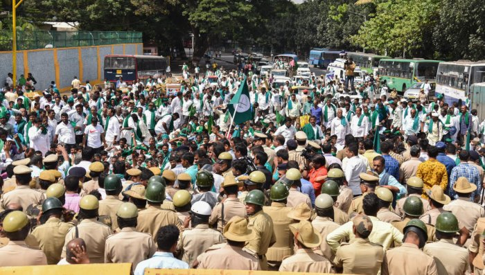 Hundreds of farmers gather in front of Freedom Park as part of their agitation in Bengaluru on Monday.
