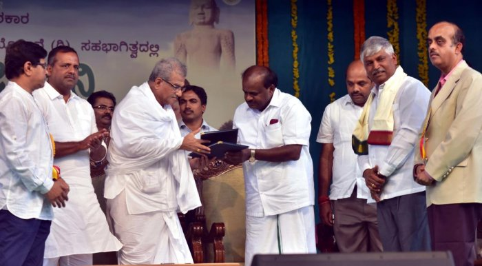 Dharmasthala Dharmadhikari D Veerendra Heggade and Chief Minister H D Kumaraswamy exchange the Memorandum of Understanding towards the rejuvenation of lakes under Kere Sanjeevini programme of the state government. District in-charge minister U T Khader an