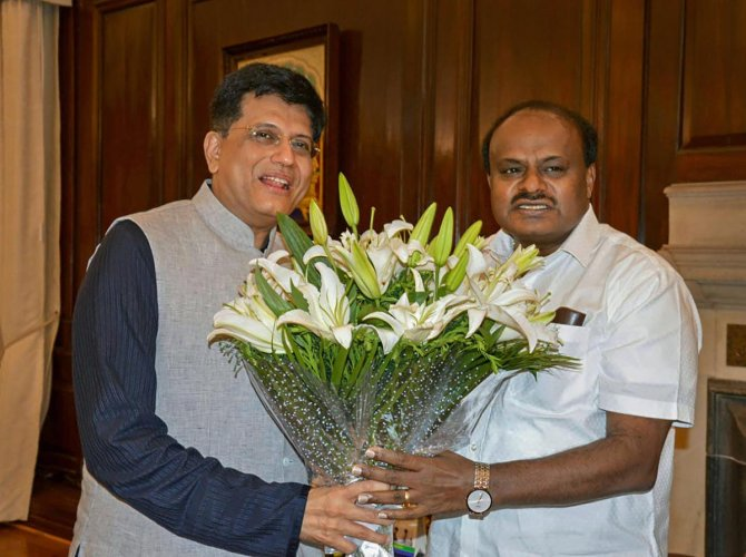 Union Coal Minister Piyush Goyal gives a bouquet to Karnataka Chief Minister HD Kumaraswamy before a meeting, in New Delhi on Wednesday, July 18, 2018. (PTI Photo)