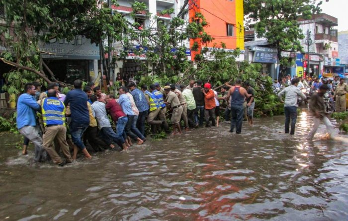 Hyderabad: People remove an uprooted tree which had blocked a street, after a thunderstorm in Hyderabad on Thursday. PIT Photo (PTI5_3_2018_000127B)