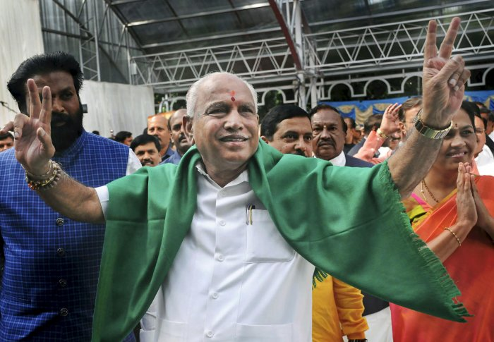 Bharatiya Janata Party (BJP) leader B. S. Yeddyurappa flashes the victory sign as he arrives at Governor's House to take oath as Chief Minister of Karnataka state, in Bengaluru. PTI Photo