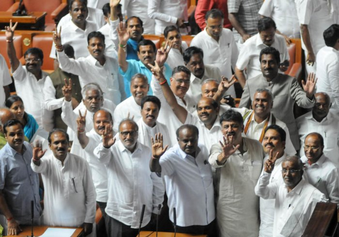 Members of the ruling party in the Karnataka Legislative Assembly show the victory sign after successfully winning the trust vote session for the newly sworn in Chief Minister of the JD(S)-Congress coalition government in the Karnataka Assembly at the Vid