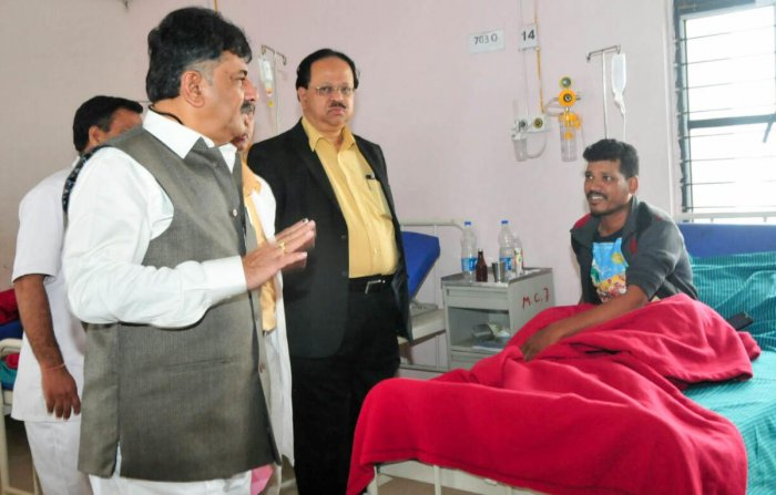 Medical education minister D K Shivakumar speaks to a patient during a surprise inspection of Victoria Hospital on Friday.