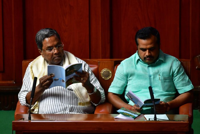 Former chief minister Siddaramaiah leafs through the budget copy during the presentation of the state budget. Government Chief Whip Ganesh Hukkeri is seen. DH Photo