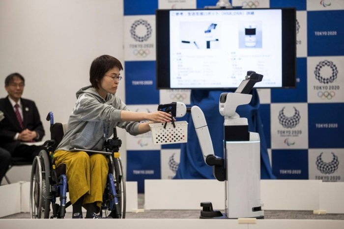 INNOVATIVE: Toyota's Human Support Robot (right) delivers a basket to a woman in a wheelchair during a demonstration of the Tokyo 2020 Robot Project. AFP