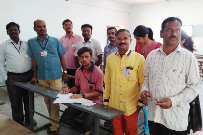 Student Prabhu Ram appears for Hindi language examination at Kottureshwara Pre-university College at Kottur in Ballari district on Friday. Some of the total 16 examination personnel are seen with him. DH photo