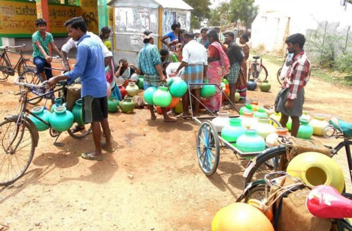 Aldoor residents collect water from a public tap.