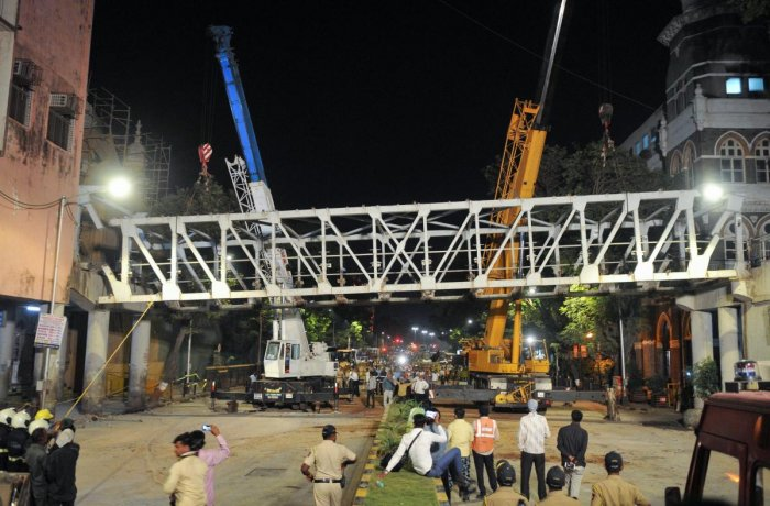 Workers dismantling the collapsed Fob Bridge at CST, in Mumbai on Friday. PTI photo
