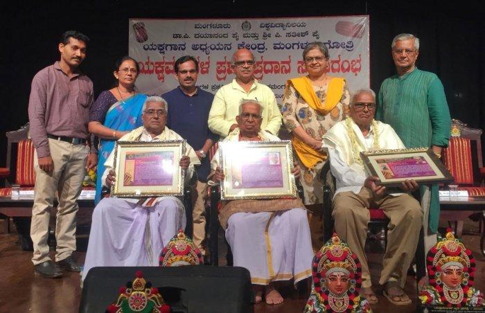 Yakshagana artistes Gode Narayana Hegde and Kumble Sundar Rao were handed the Yakshamangala awards while Prof G S Bhat Sagar receives the Yakshamangala Krithi award at a programme at Mangalore University.