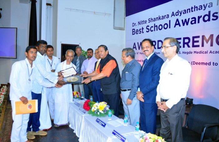 Former Lokayukta Justice N Santosh Hegde hands the Dr Nitte Shankara Adyanthaya Memorial Best School Award at a programme held at Deralakatte on Saturday.