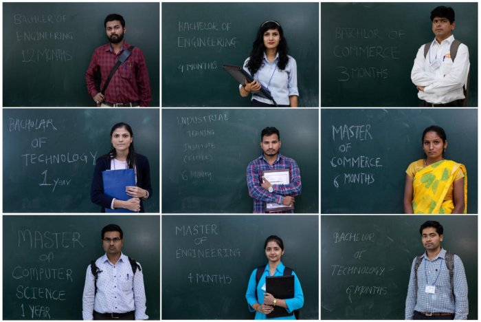 A combo shows unemployed people posing in front of a chalkboard with their qualifications during a job fair in Chinchwad. REUTERS