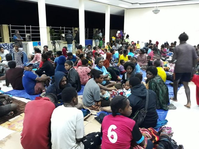 This handout picture taken and released by Indonesia's Badan Nasional Penanggulangan Bencana (BNPB), the accident mitigation agency, on March 17, 2019 shows local residents gather at a temporary shelter in Sentani, near the provincial capital of Jayapura, as floodwaters triggered by torrential rain swarmed the area. At least 42 people have been killed by flash floods in IndonesiaÕs eastern Papua province, an official said. - At least 42 people have been killed by flash floods. AFP photo