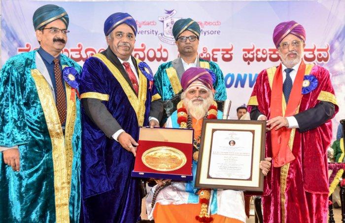 University of Mysore Vice Chancellor Prof. G Hamankumar felicitating with Honorary Doctorate to Somanakatte Sri Kadasiddeshwara Math Nonavinakere, Tiputuru Karivrashabha Deshikendra Shivayogishwara Swamiji during the 99th Annual Convocation of University
