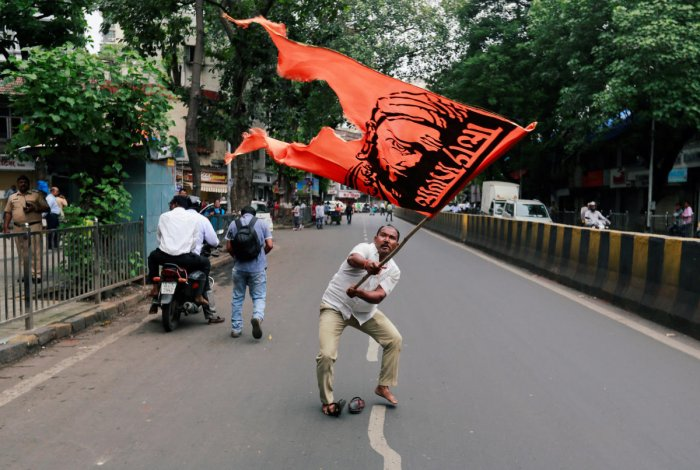 A man waves a flag as he blocks a road during a protest, organised by Maharashtra state's Maratha community, to press their demands for reserved quotas in government jobs and college places for students in Mumbai, July 25, 2018. REUTERS photo.
