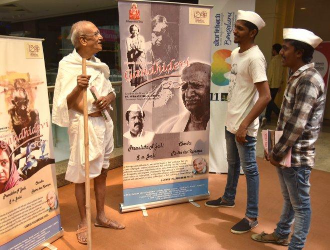 Vemgal Somashekar dressed like Mahatma Gandhi stands next to Gandhidevi film poster at BIFFes 2019. DH Photo by SK Dinesh