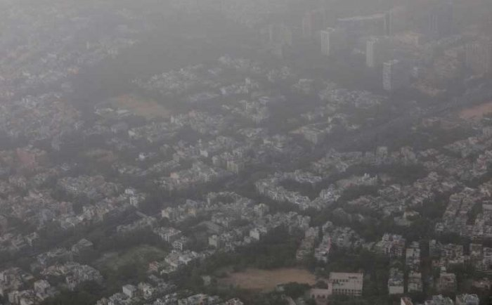 Buildings are seen blanketed by haze and dust on the outskirts of New Delhi, India, June 14, 2018. REUTERS