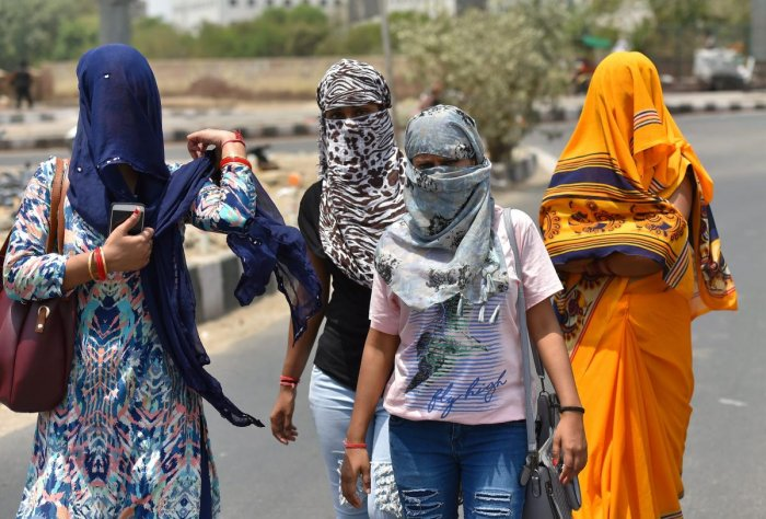 Women cover their faces with scarves to protect themselves from heat in New Delhi. PTI File Photo