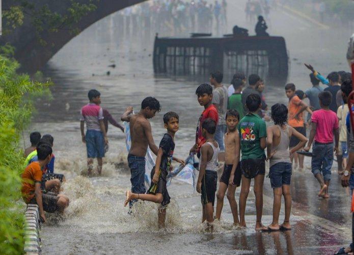 Children play near a waterlogged street under Minto Bridge during a monsoon rain in New Delhi on Monday. PTI