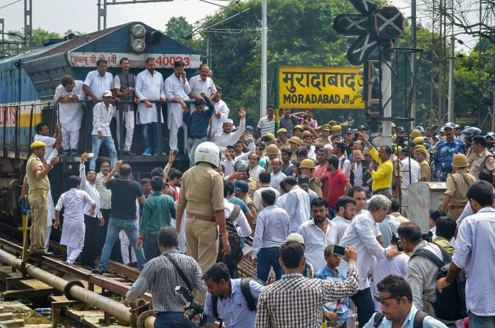 Congress Party supporters stop a train during 'Bharat Bandh' protest called by Congress and other parties against fuel price hike and depreciation of the rupee, in Moradabad, Monday, Sept 10, 2018. (PTI Photo)