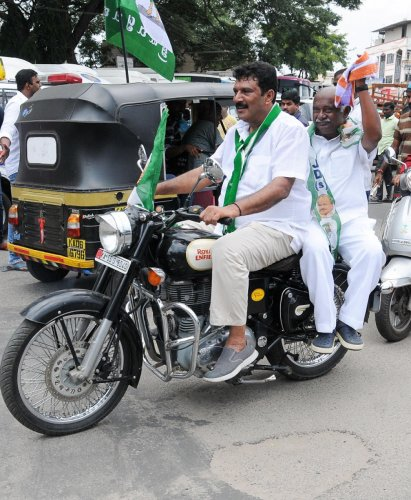 time to violate rules: JD(S) leader Azeez Abdullah takes party state president A H Vishwanath for a ride, on a mobike without helmets, in Mysuru, on Monday.
