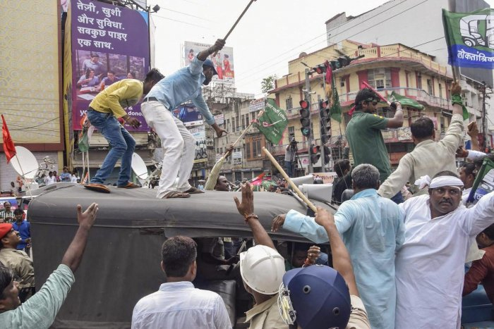 Jan Adhikar Party activists climb on a police vehicle during the Bharat Bandh called over fuel price hike in Patna on Monday. PTI