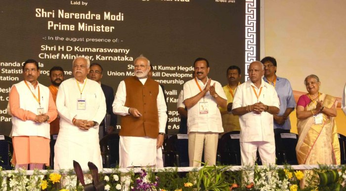 Prime Minister Narendra Modi launches various development projects at a programme in Hubballi on Sunday. Union Minister Sadananda Gouda, State Minister R V Deshpande, MP Pralhad Joshi, B S Yeddyurappa and Infosys founder Sudha Murthy are seen. DH Photo