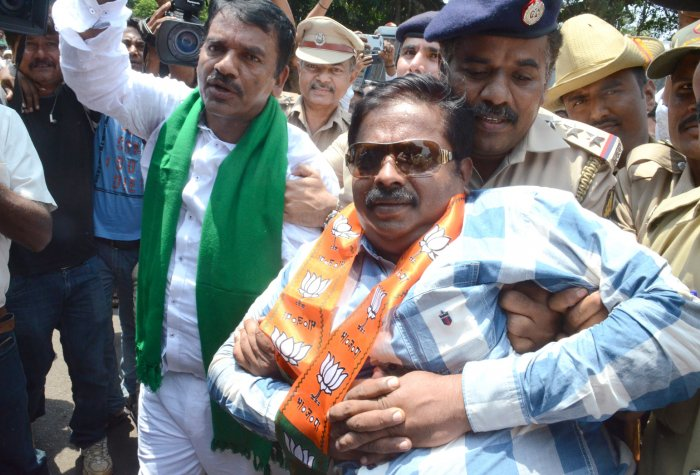 BJP MLAs Abhay Patil and Anil Benke being detained by police during bandh call given by BJP demanding waiver of farmers loans and staging sit-in protest at Channamma Circle in Belagavi on Monday. (DH Photo)