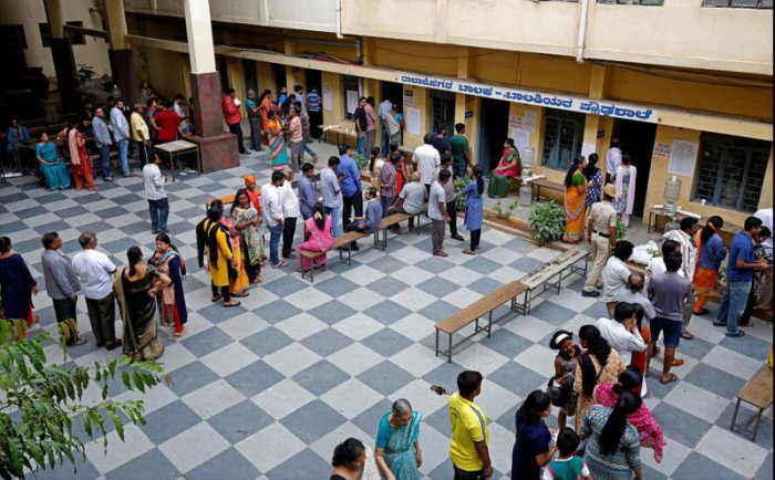 Voters wait in queues to cast their ballot outside a polling station during Karnataka assembly elections in Bengaluru, India, May 12, 2018. REUTERS